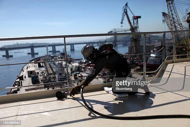 A worker polishes the deck of the Jose de Alencar vessel a Petroleo Brasileiro SA oil tanker under construction at the Maua SA shipyard in Niteroi...