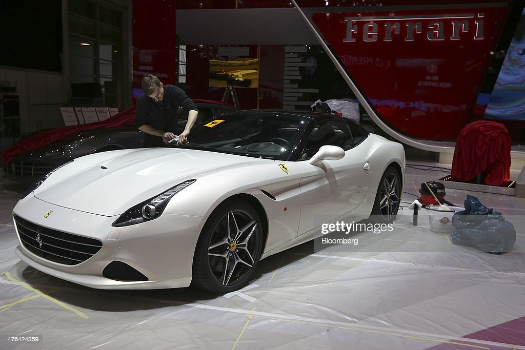 A Worker Polishes The Windscreen Of A White Ferrari California T