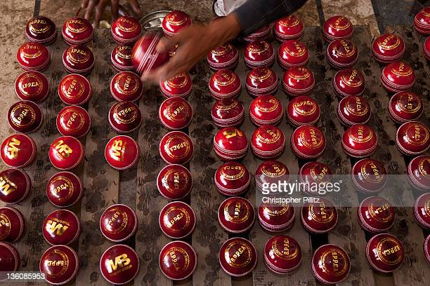 Worker polishing hand-made cricket balls at the MB cricket bat and ball factory, Sialcot, Pakistan, 25th March 2011. The company makes bats for the...