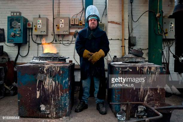 A worker poses for a portrait as he makes molten bronze before casting BAFTA masks during a photo call at the New Pro Foundries west of London on...