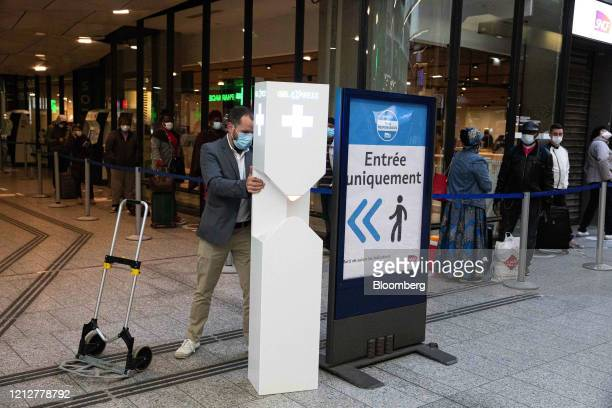 A worker positions a hand gel dispensing unit at Gare Montparnasse railway station in Paris France on Tuesday May 12 2020 The Paris metro authority...