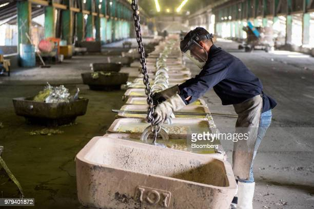 A worker positions a lifting chain onto ingot molds at the Iran Aluminium Co plant in Arak Iran on Tuesday June 19 2018 As OPEC oil ministers meet in...