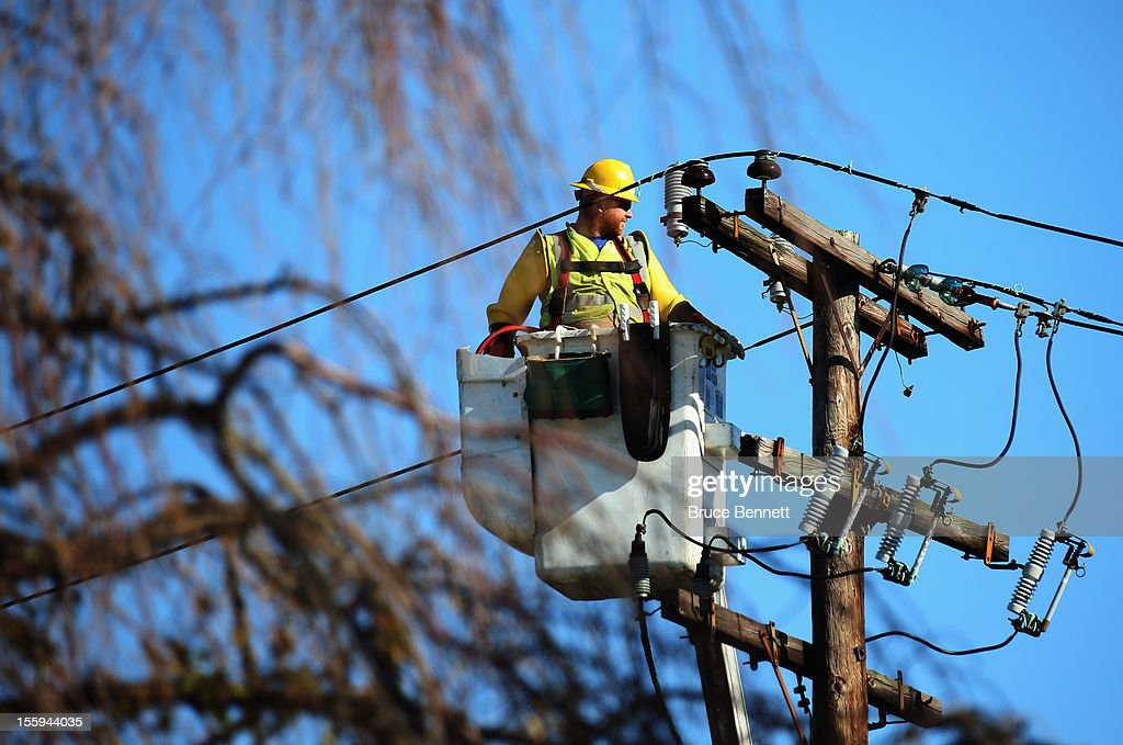 A worker positions himself to repair electrical lines as Long Islanders continue their clean up efforts in the aftermath of Superstorm Sandy on November 9, 2012 in Plainview, New York. New York Gov. Andrew M. Cuomo has said that the economic loss and damage to homes and businesses caused by Sandy could total $33 billion in New York, according to published reports.