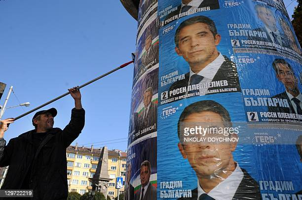 A worker posts election posters of Bulgaria's centreright ruling GERB party presidential candidate Rosen Plevneliev in Sofia on October 20 2011...