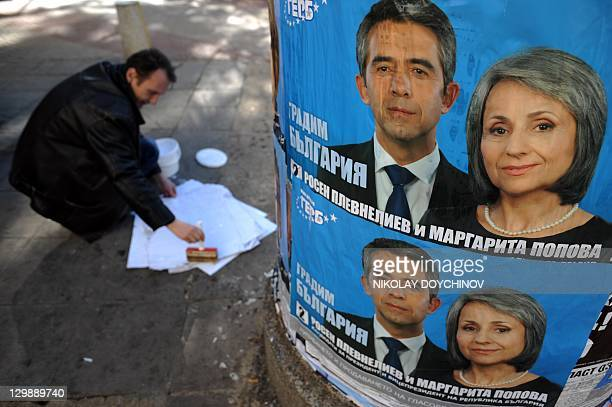 A worker posts election posters of Bulgaria's centreright ruling GERB party presidential candidate Rosen Plevneliev in Sofia on October 21 2011...
