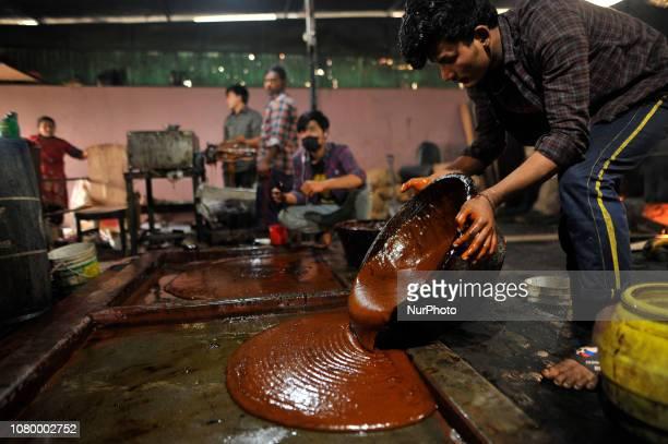 A worker pour semi Hard molasses to cooldown to prepare molasses Chaku at Tokha Kathmandu Nepal on Thursday January 10 2019 Molasses Chaku is usually...