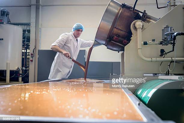 worker pouring confectionery fudge in chocolate factory - chocolate factory stock photos and pictures