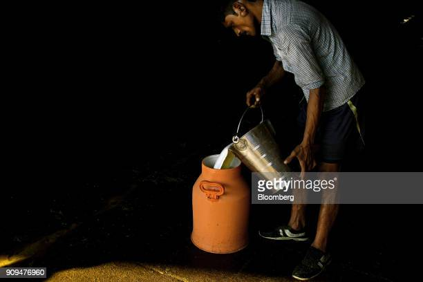 A worker pours a bucket of milk into a storage can at the Sri Krishna Gaushala on the outskirts of New Delhi India on Sunday Jan 21 2018 The nursing...