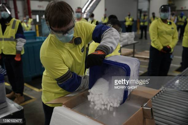 Worker pours dry ice into boxes containing the Pfizer-BioNTech Covid-19 vaccine as they are prepared to be shipped at the Pfizer Global Supply...