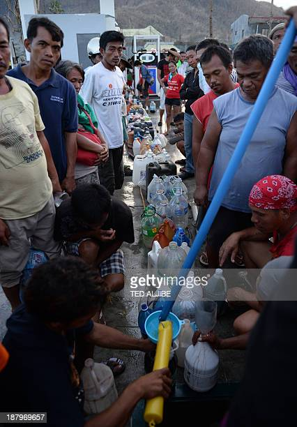 Worker pours free petrol into a plastic contaner held by a Typhoon-affected resident at a destroyed gasoline station in Tacloban city, Leyte...