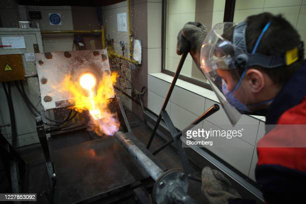 Worker pours molten gold from a crucible into a mold during the casting of gold ingots at the Uralelectromed Copper Refinery, operated by Ural Mining...