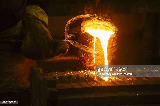 A worker pours molten gold into a mold during the refining of bullion at a refinery