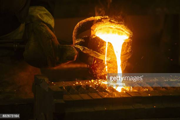 A worker pours molten gold into a mould during the refining of bullion at the Rand Refinery Ltd plant in Germiston South Africa on Wednesday Aug 16...