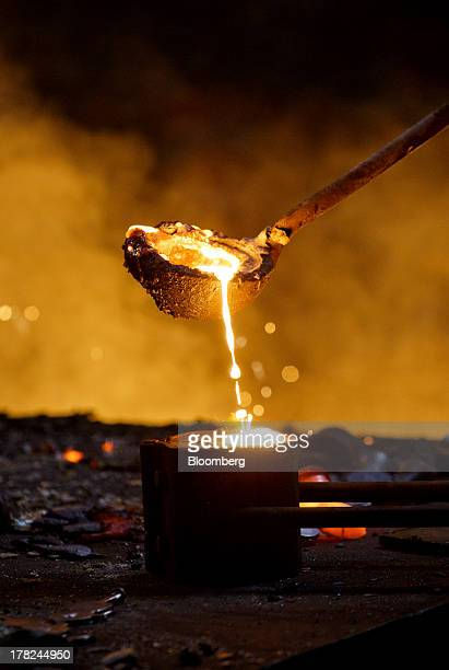 Worker pours molten steel from a ladle into a mould at ArcelorMittal's steel plant in Ostrava, Czech Republic, on Monday, Aug. 26, 2013....