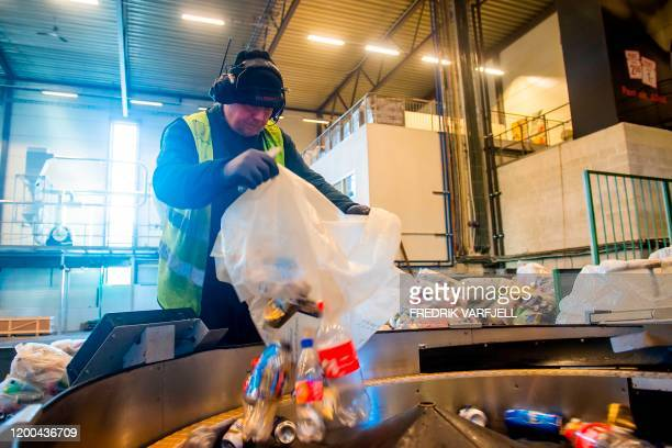Worker pours plastic bottles and aluminium cans in to a machine at a recycling plant of the company Infinitum, in Fetsund, southeastern Norway, on...