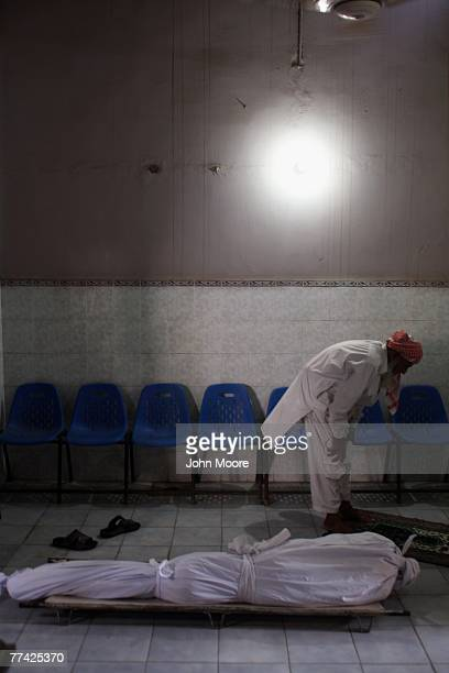 A worker prays next to an unclaimed body at the Edhi Foundation morgue October 20 2007 in Karachi Pakistan Two days after a suicide bomber attacked...