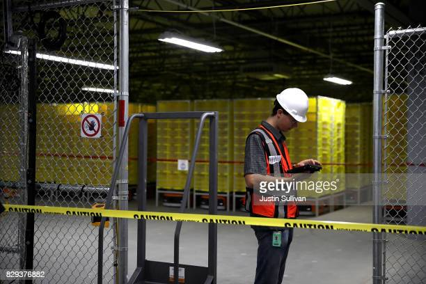 A worker preapres to test robotic technology and vision systems at a new Amazon fulfillment center on August 10 2017 in Sacramento California Amazon...