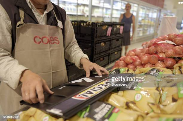 A worker prepares a board displaying prices at a Coles supermarket operated by Wesfarmers Ltd in the Richmond area of Melbourne Australia on Friday...