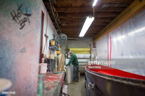 A worker prepares a canoe for its fibreglass shell at the Holy Cow Canoe Co production facility in Guelph Ontario Canada on Thursday March 1 2018...