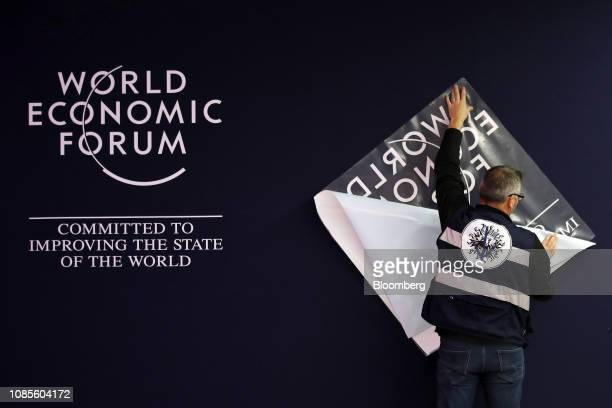 A worker prepares a logo transfer for a wall inside the Congress Center the venue for the World Economic Forum in Davos Switzerland on Sunday Jan 20...