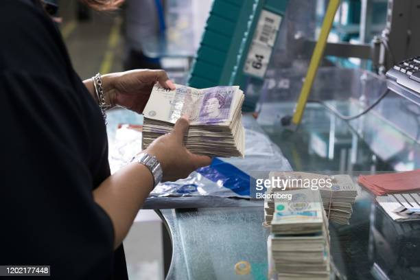 Worker prepares bundles of old British pound banknotes to feed into a note sorting machine in a warehouse operated by G4S Plc in London, U.K. On...