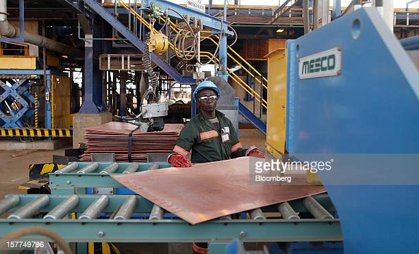 A worker prepares copper sheets for binding together into bundles at a processing plant in the Mutanda copper and cobalt mine in Mutanda Katanga...