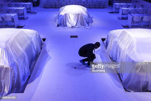 A worker prepares covered MercedesAMG automobiles for a presentation at the MercedesBenz AG media night at the Piscine Molitor prior to the opening...