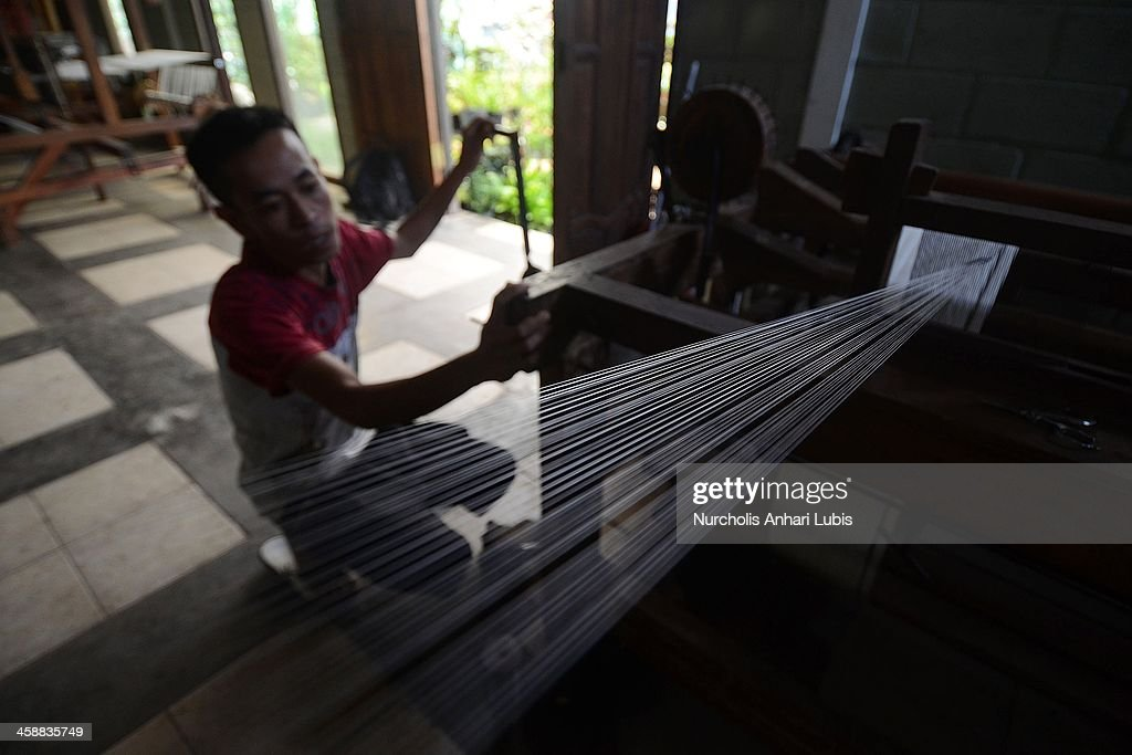 A worker prepares fibres to be used in the making of silk fabrics at a production unit on December 21, 2013 in Bogor, Indonesia. The Indonesian silk industry is well established although generally consisting of small and local producers in contrast to more developed competition and industry seen in countries such as Japan, China and Thailand. The silk produced is used in the manufacture of traditional handicrafts including batik clothing and textiles.