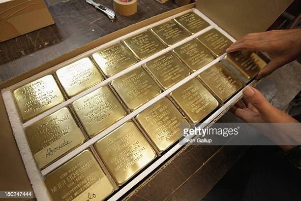 Worker prepares finished Stolpersteine, which are concrete cobblestones afixed with a brass commemorative plaque, for shipping at the Stolpersteine...