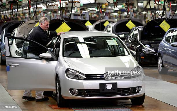 Worker prepares finished Volkswagen Golf cars to be driven off the end of the assembly line at the VW factory on March 8, 2010 in Wolfsburg, Germany....
