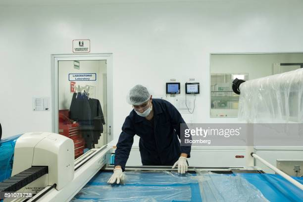A worker prepares material for precision cutting at the Tighitco Inc manufacturing facility in San Luis Potosi Mexico on Thursday Nov 16 2017 With...
