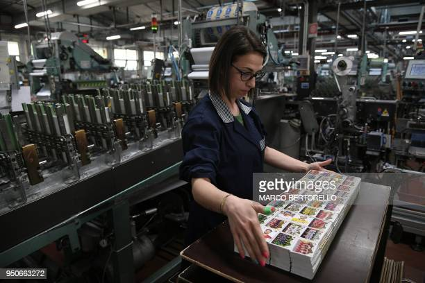 Worker prepares packages of collectible cards featuring football players for the 2018 Russia football World Cup at the Panini Group factory on April...