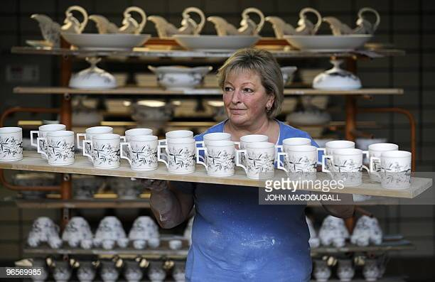 A worker prepares porcelain items to be glazed at the Meissen porcelain manufacture in Meissen January 20 2010 The Meissen porcelain manufacture a...