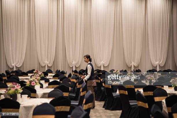 A worker prepares tables in a banquet hall at a hotel of the Inje Speedium resort complex where a delegation of North Korean cheerleaders attending...