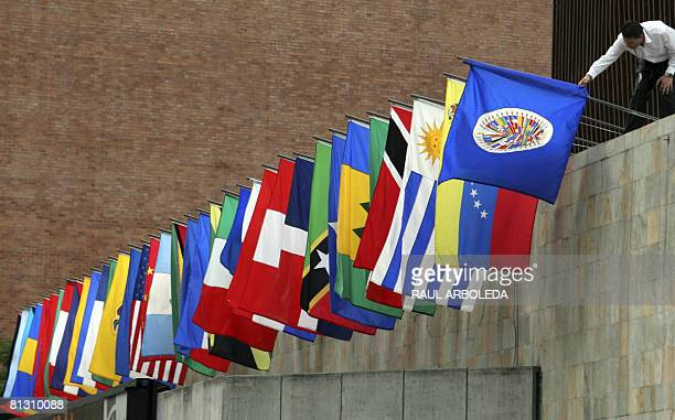 A worker prepares the flags of the Organization of American States outside a press conference on May 30 2008 in Medellin The 38th regular session of...
