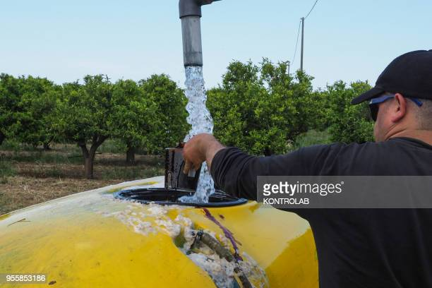 A worker prepares the pesticides antiparasitic mixture on a farm The use of pesticides is being reduced all over the world as they pollute...