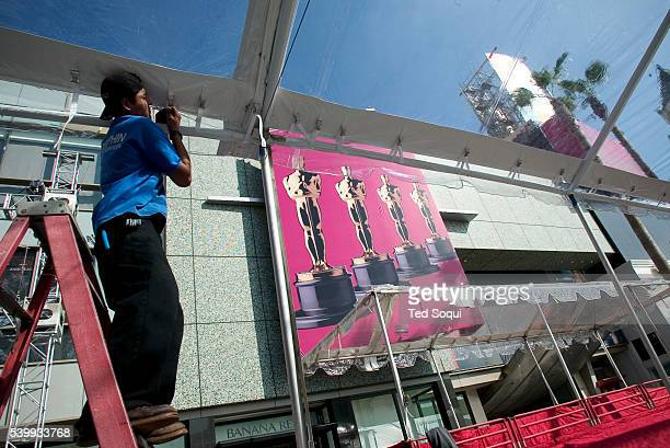 A worker prepares the redcarpet for celebrity arrivals and global media on Hollywood Boulevard at Highland for the 77th annual Academy Awards® at the...