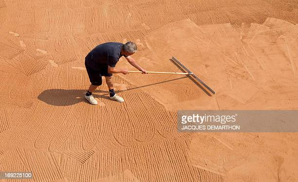 A worker prepares the surface of clay court number 1 of Roland Garros' tennis stadium in Paris on April 25 2011 The French tennis tournament of...
