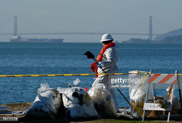 A worker prepares to clean oil from rocks at Point Bonita November 27 2007 in Richmond California Almost three weeks after the freighter ship Cosco...