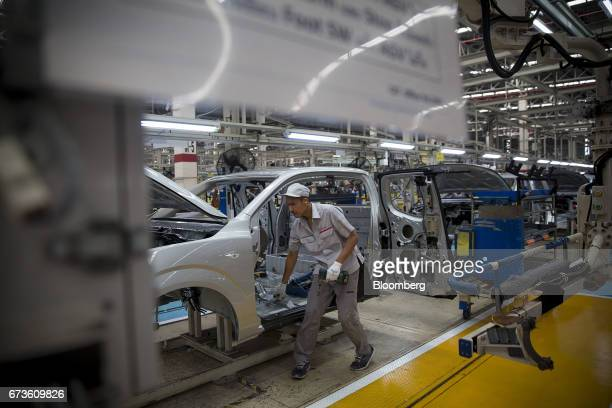 A worker prepares to install a component onto a Nissan Motor Co Navara pickup truck on an assembly line at the company's plant in Samut Prakan...