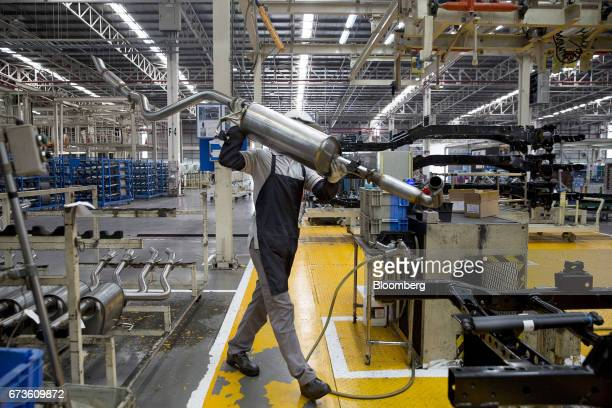 A worker prepares to install an exhaust pipe on the chassis of a Nissan Motor Co Navara pickup truck on an assembly line at the company's plant in...