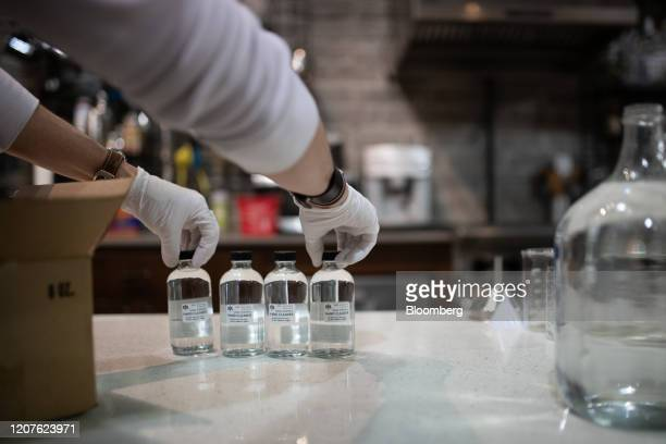 A worker prepares to pack bottles of hand sanitizer solution made from distilled alcohol byproducts at the Glass Distillery in the SoDo neighborhood...