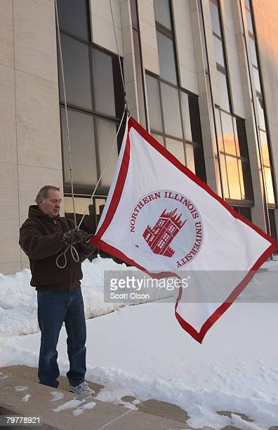 A worker prepares to raise the university flag on the campus of Northern Illinois University following yesterday's shooting at Cole Hall February 15...