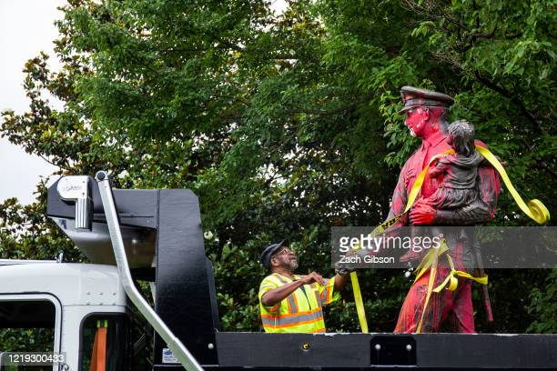 Worker prepares to remove a police memorial statue covered in red paint by protesters on June 11, 2020 in Richmond, Virginia. Protesters also tore...