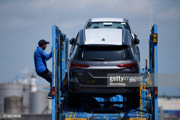 A worker prepares to unload Toyota Motor Cop vehicles from a car carrier trailer at the Nagoya Port in Nagoya Japan on Tuesday July 31 2018 Japan is...