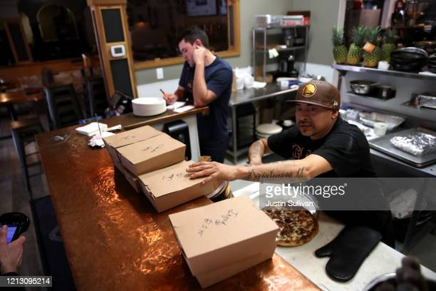 A worker prepares togo orders at Creekside Pizza and Taproom on March 17 2020 in San Anselmo California Restaurants are only allowed to offer food to...