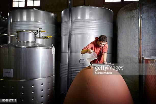 Worker preparing concrete tank for fermentation