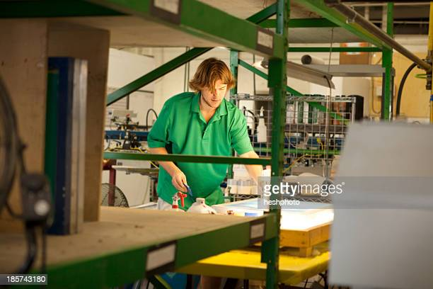 worker preparing frame in screen printing workshop - heshphoto stockfoto's en -beelden