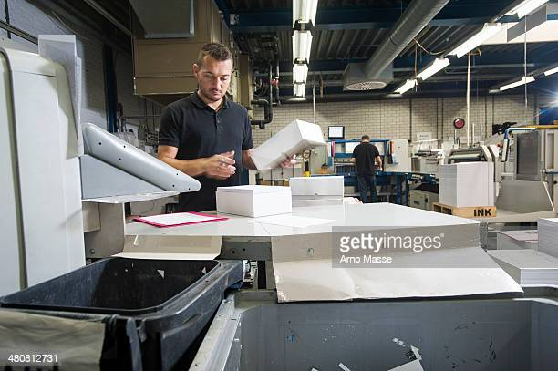 Worker preparing paper for machine in print workshop