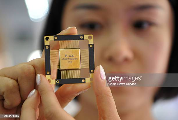 A worker presents a chip for fifthgeneration mobile networks at China Electronics Technology Group stand during the 1st Digital China Summit at...
